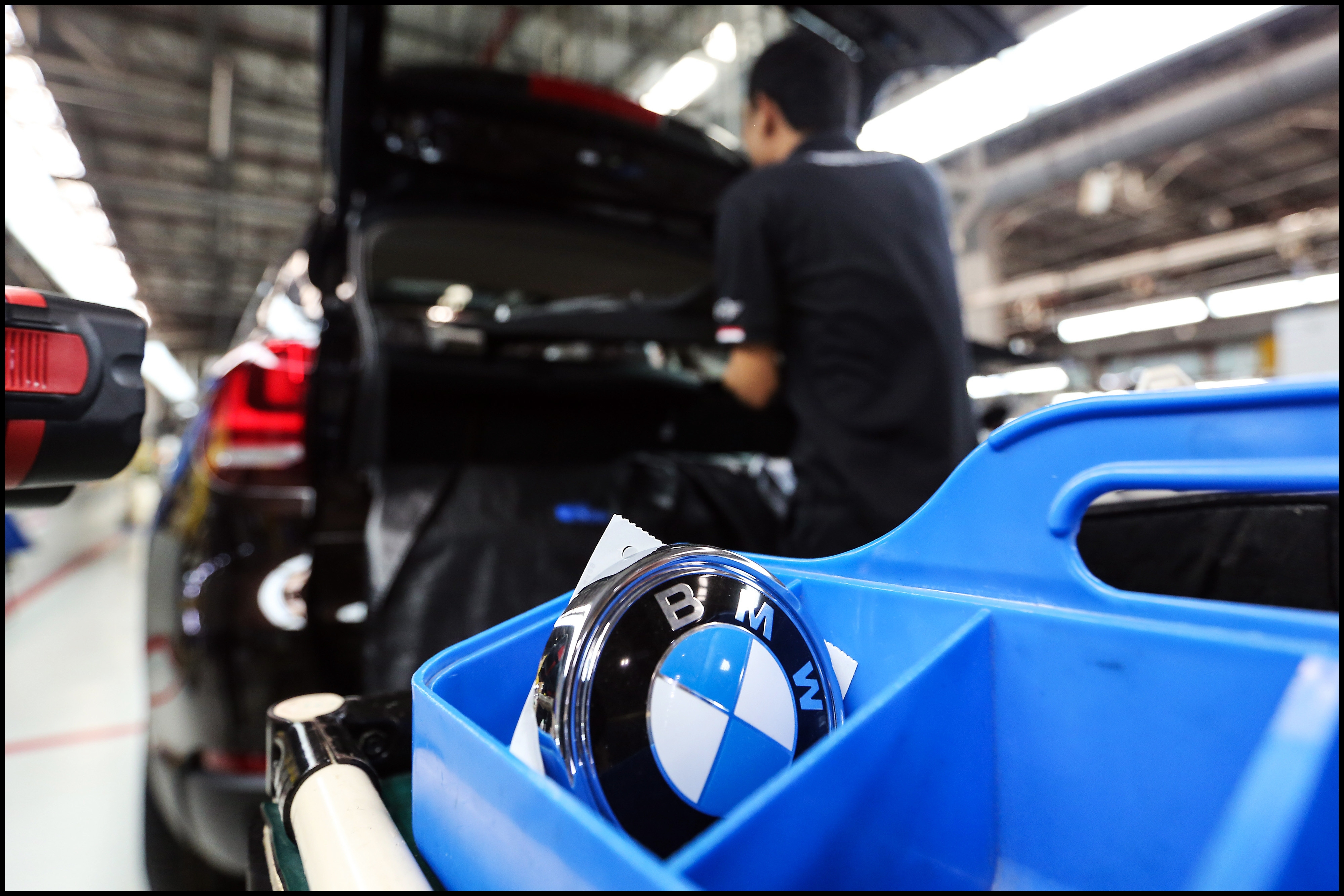 A BMW AG badge sits in a tray before being mounted onto an X5 vehicle at