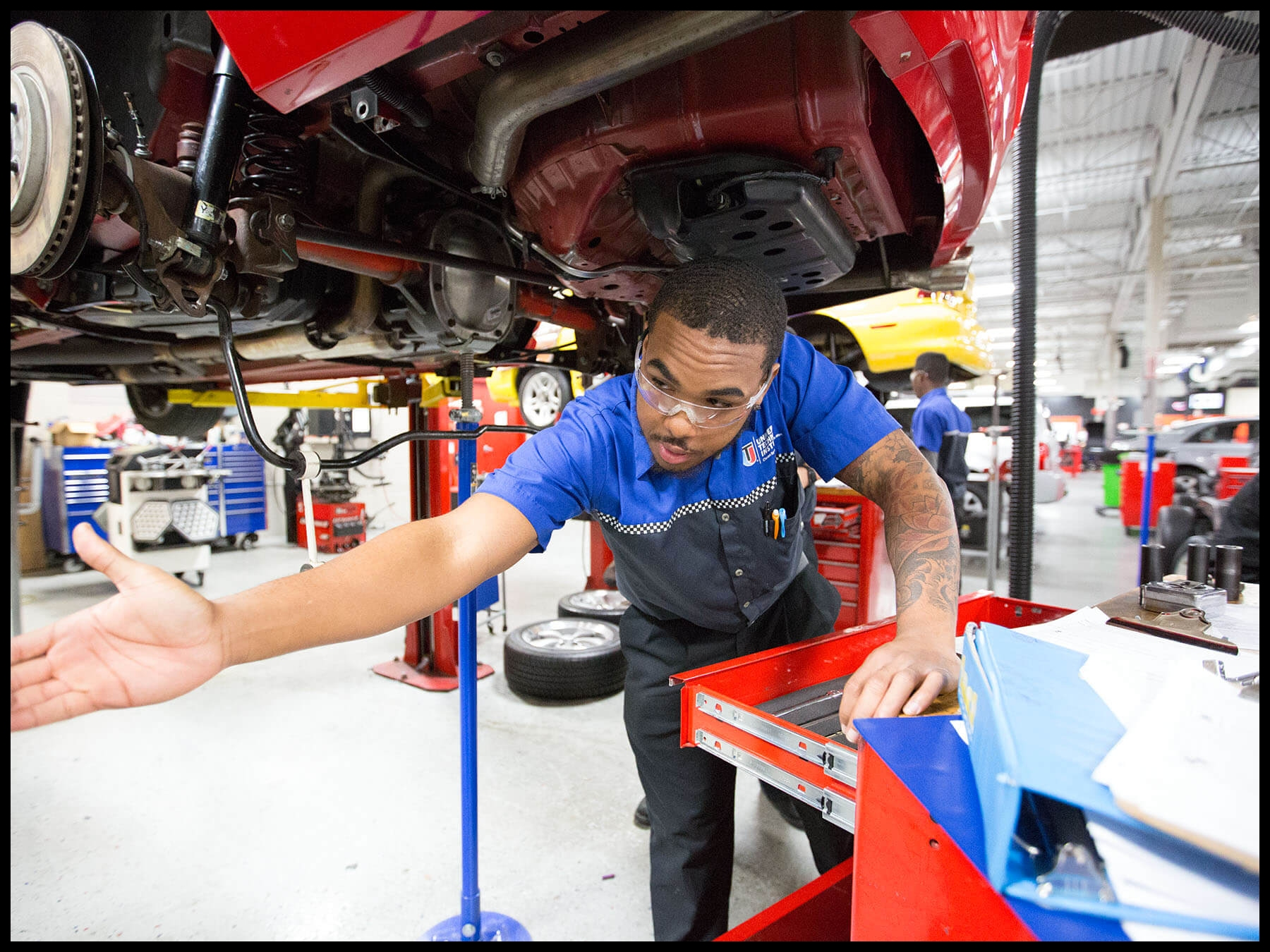 UTI student working underneath a car in the auto lab